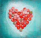 La forme de coeur a coupé en tranches des fraises sur le fond en bois chic minable de bleu de turquoise Photos libres de droits
