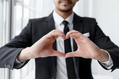 La forme de coeur d'exposition d'homme d'affaires avec sa main Images stock