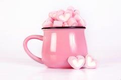 La forme de coeur de guimauve dans la tasse sur le fond rose avec amour Photos stock
