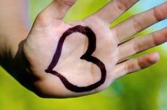 La forme de coeur drawed sur une main humaine masculine Images stock