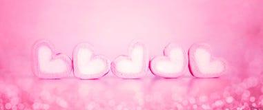 La forme de coeur de guimauve dans la tasse sur le fond rose avec amour Photo libre de droits
