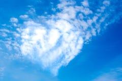 La forme de coeur opacifie un jour ensoleillé, fond de ciel bleu Images stock