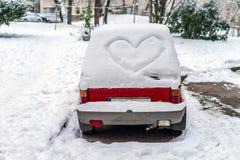 La forme de coeur sur la neige a couvert la fenêtre arrière de voiture image stock