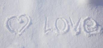La forme et l'amour de coeur expriment écrit dans la neige Photo stock