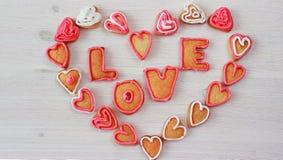 La forme et le mot AIMENT de coeur les biscuits faits maison de valentine Photographie stock libre de droits