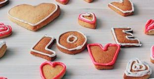 La forme et le mot AIMENT de coeur les biscuits faits maison de valentine Photos libres de droits