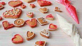 La forme et le mot AIMENT de coeur les biscuits faits maison de valentine avec des sacs de pâtisserie Photo stock