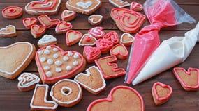 La forme et le mot AIMENT de coeur les biscuits faits maison de valentine avec des sacs de pâtisserie Images libres de droits