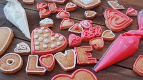 La forme et le mot AIMENT de coeur les biscuits faits maison de valentine avec des sacs de pâtisserie Image stock