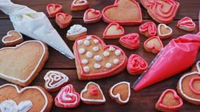 La forme et le mot AIMENT de coeur les biscuits faits maison de valentine avec des sacs de pâtisserie Photographie stock