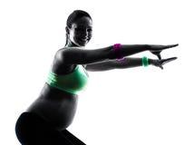 La forme physique de femme enceinte exerce la silhouette image stock