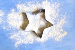 La forme pour des biscuits d'étoile sur le conseil bleu avec de la farine blanche Photos libres de droits
