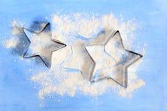 La forme pour des biscuits d'étoile sur le conseil bleu avec de la farine blanche Image stock