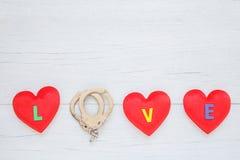 La forme rouge de coeur avec le mot d'amour et l'O remplacent par le dispositif d'accrochage sur le blanc Photographie stock