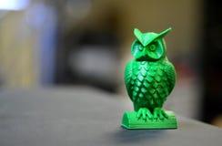 La forme verte sous forme de petit hibou créé sur le fond d'obscurité de l'imprimante 3d Photo stock
