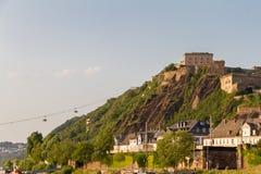 La fortaleza de Ehrenbreitstein se bañó en la luz y el cablecarril de la tarde que lo conectaban con Coblenza, Alemania foto de archivo libre de regalías