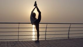 La forte e bella donna si appoggia la barra trasversale e si scalda Getta le sue gambe attraverso indietro flessibilità seaside archivi video