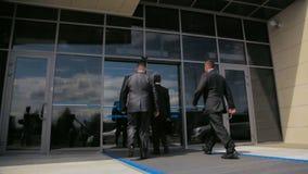 La forte guardia del corpo in vestito convenzionale guarda intorno e segue la persona protetta archivi video
