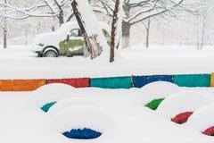La forte nevicata cade campo da giuoco ed automobile addormentati Immagine Stock