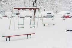 La forte nevicata cade campo da giuoco ed automobile addormentati Fotografia Stock Libera da Diritti