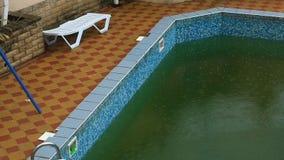 La forte pluie tombe dans une piscine Pas saison, piscine abandonnée sale banque de vidéos