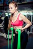 La forte ragazza atletica con capelli biondi lunghi utilizza la banda verde di allungamento mentre si esercita in palestra Fotografia Stock
