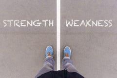 La forza e la debolezza mandano un sms a sulla terra, sui piedi e sulle scarpe dell'asfalto sopra fotografia stock libera da diritti