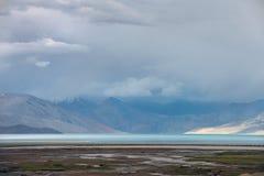 La foschia di mattina su un lago della montagna, una striscia blu dell'acqua, nei precedenti le montagne affonda nella foschia, a Fotografia Stock Libera da Diritti
