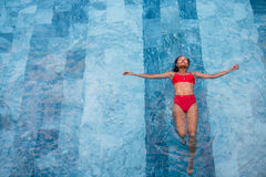 La foto aérea de la visión superior de un modelo atractivo atractivo en el traje de baño blanco está gozando se relaja en piscina Imagen de archivo libre de regalías