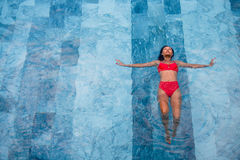 La foto aérea de la visión superior de un modelo atractivo atractivo en el traje de baño blanco está gozando se relaja en piscina Fotografía de archivo libre de regalías