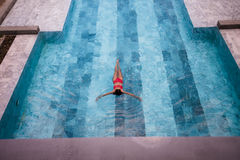 La foto aérea de la visión superior de un modelo atractivo atractivo en el traje de baño blanco está gozando se relaja en piscina Fotos de archivo libres de regalías