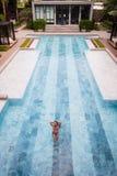 La foto aérea de la visión superior de un modelo atractivo atractivo en el traje de baño blanco está gozando se relaja en piscina Imágenes de archivo libres de regalías