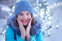 La foto al aire libre de la hembra hermosa joven camina en la calle, lleva la ropa elegante del invierno, admira luces mágicas, h foto de archivo libre de regalías