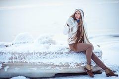 La foto al aire libre de la moda de la mujer magnífica con el pelo rubio largo lleva la capa blanca lujosa Imagenes de archivo