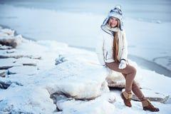 La foto al aire libre de la moda de la mujer magnífica con el pelo rubio largo lleva la capa blanca lujosa Foto de archivo libre de regalías