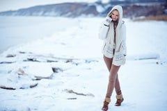 La foto al aire libre de la moda de la mujer magnífica con el pelo rubio largo lleva la capa blanca lujosa Imagen de archivo libre de regalías