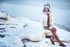 La foto al aire libre de la moda de la mujer magnífica con el pelo rubio largo lleva la capa blanca lujosa Fotos de archivo libres de regalías