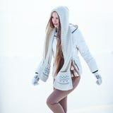 La foto al aire libre de la moda de la mujer magnífica con el pelo rubio largo lleva la capa blanca lujosa Fotos de archivo