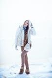 La foto al aire libre de la moda de la mujer magnífica con el pelo rubio largo lleva la capa blanca lujosa Fotografía de archivo