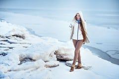 La foto al aire libre de la moda de la mujer magnífica con el pelo rubio largo lleva la capa blanca lujosa Foto de archivo