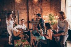 La foto alta vicina che si diverte i compagni dei migliori amici della riunione va in giro la solista vocale la chitarra del gioc immagini stock