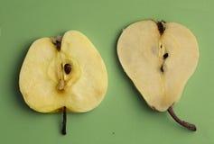 La foto ascendente cercana de la pera y de la manzana en cocina verde sube Imágenes de archivo libres de regalías