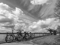 La foto blanco y negro de 3 parqueó bicicletas y un cielo nublado imagen de archivo