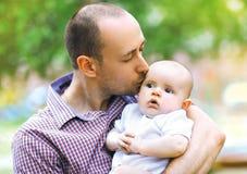 La foto caliente, sensual, padre besa al pequeño bebé fotos de archivo