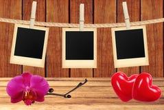 La foto carda la ejecución en cuerda en pinzas, orquídea y corazones rojos Fotos de archivo