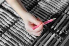 La foto de B&W del color dibujó a lápiz con el foco en el lápiz rosado que se sostiene por el niño Fotografía de archivo