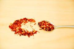 La foto de chiles rojos forma escamas con una cuchara de plata Foto de archivo libre de regalías