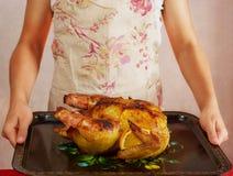 La foto de la comida del hombre irreconocible en delantal está sosteniendo el pollo frito foto de archivo libre de regalías