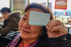 La foto de Defocus de viejas mujeres asiáticas hace una demostración del cutie su boleto de tren imagenes de archivo
