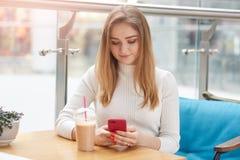 La foto de encantar a la mujer rubia utiliza el teléfono elegante, se sienta en el sofá en el café, redes sociales de los surfes, foto de archivo